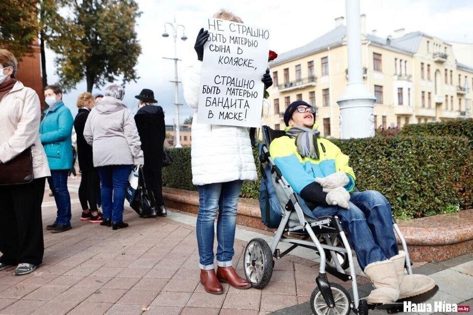 Frau hält Plakat neben Kind im Rollstuhl